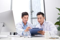 Two doctors holding and talking about patient on office stock photos