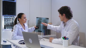 Two doctors in the hospital. Young woman intern showing doctor x-ray of the lungs. Professional adult therapist explaining what disease has patient. Caucasian stock footage