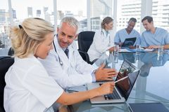 Two doctors with a laptop. In a bright office Stock Photos