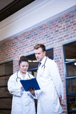 Two doctors looking at clipboard and discussing near library Stock Photos