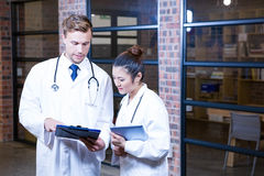 Two doctors looking at clipboard and discussing near library Stock Images