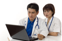 Two Doctors looking at computer on their desk Stock Images