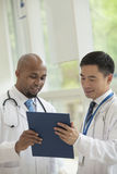 Two doctors looking down and consulting over medical record in the hospital Royalty Free Stock Image