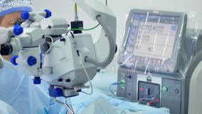 Two doctors are looking into an ophthalmological machine in an operating room. Two doctors male and female, are standing and looking into the ophthalmological stock footage