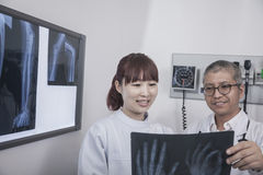 Two doctors looking at an x-ray of hand bones Stock Photography