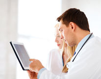 Two doctors looking at x-ray on tablet pc. Healthcare and medical - two doctors looking at x-ray on tablet pc stock images