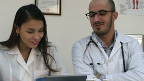 Two doctors looking at something funny on the tablet and laughing stock video footage