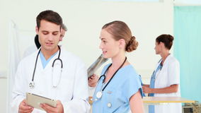 Two doctors looking at tablet computer with their colleagues behind. HD video of two doctors looking at tablet computer with their colleagues behind stock footage