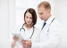 Two doctors looking at tablet pc Royalty Free Stock Images