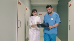 Two doctors man and woman walking in the hallway of the clinic and talk to each other. Shooting with a Steadicam 4k stock footage