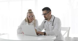 Two doctors in medical gowns are sitting at a white table and using a laptop. A doctor and a nurse in glasses discuss the patient`s treatment. Male doctor stock video footage