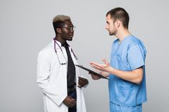 Two doctors meeting and consulting each other on gray background. Caucasian doctor and afroamerican doctor talking abount pacient stock images