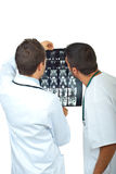 Two doctors men examine magnetic resonance. Back of two doctors men examine magnetic resonance imaging isolated on white background,check also  Medical Stock Photos