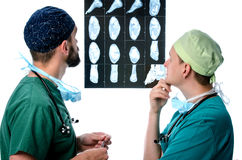 Two doctors men in scrubs studying x-ray picture of the patient. Two doctors men in green scrubs studying x-ray picture of the patient Stock Images
