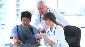 Two doctors and a nurse looking at an xray. In a bright room stock video footage