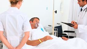 Two doctors with a patient in his bed. At the hospital stock footage