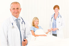 Two doctors with patient lying in bed royalty free stock photography