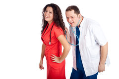 Two doctors playing with stethoscope. Couple of young doctors having fun, looking at camera. Man dressed in blue and white scrubs listens with stethoscope the Stock Photography