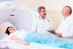Two doctors preparing patient to CT scanner procedure. Two doctors discuss preparing patient to CT scan procedure Royalty Free Stock Images