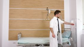 Two doctors pulling a hospital bed in the room. They are arranging the room for a very important patient stock footage