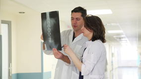 Two Doctors with X-ray Image. Two Doctors in Clinic's Corridor with X-ray Image stock video footage