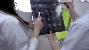 Two doctors with x-ray prints. Two doctors examining patients X-rays in hospital stock video