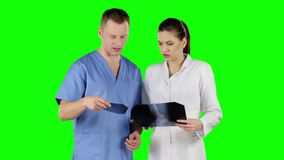 Two doctors with x-ray prints. Green screen. Two doctors with x-ray prints, workflow in the hospital, blue workwear, green screen stock video footage