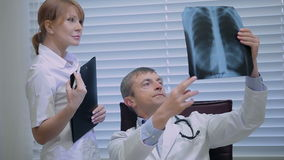 Two doctors with x-ray prints. Doctors in a meeting examining xray. Serious doctors looking together at an xray. Hospital, profession, people and medicine stock footage