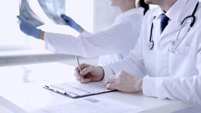 Two doctors with x-ray prints and papers. Closeup of two doctors with x-ray prints and papers stock video