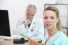 Two doctors at reception desk Royalty Free Stock Image