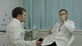 Two doctors relaxing at modern hospital indoors. Young male doctors relaxing at modern hospital indoors, speaking about life and work, long short stock video footage