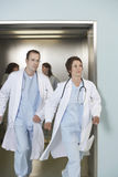 Two Doctors Running Out Of Elevator Stock Photo