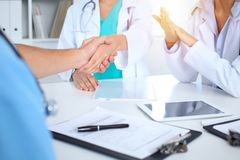 Two doctors shaking hands to each other at meeting. Teamwork and agreement in medicine royalty free stock image