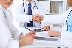 Two doctors shaking hands to each other sitting at the table in hospital office Royalty Free Stock Images