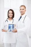 Two doctors showing x-ray on tablet pc. Healthcare, medical and radiology - two doctors showing x-ray on tablet pc stock images
