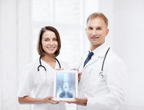 Two doctors showing x-ray on tablet pc. Healthcare, medical and radiology concept - two doctors showing x-ray on tablet pc royalty free stock photos