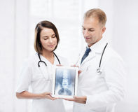Two doctors showing x-ray on tablet pc. Healthcare, medical and radiology concept - two doctors showing x-ray on tablet pc royalty free stock photo