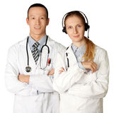 Two doctors smiles at camera. Isolated on different backgrounds Royalty Free Stock Photography
