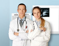 Two doctors smiles at camera. Isolated on different backgrounds Royalty Free Stock Photo