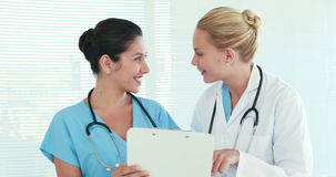 Two doctors speaking together and looking at clipboard stock footage