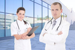 Two doctors standing against modern hospital building Stock Images