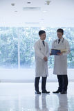 Two doctors standing, looking down, and consulting over medical record in the hospital Stock Photography