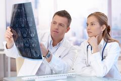 Two doctors studying x-ray image consulting. Two doctors studying x-ray image, consulting in bright office royalty free stock photography