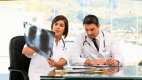 Two doctors taking notes about a scan. At the hospital stock video footage