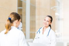 Two doctors talking in the lobby of the hospital Stock Photos
