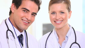 Two doctors are talking. Two doctors wearing white coat are talking stock footage