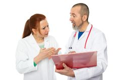 Two doctors two opinions. Two doctors discussing a patient file Stock Photography