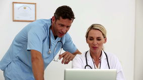 Two doctors using a laptop together in their office stock video footage