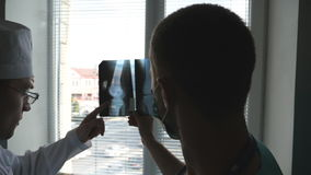 Two doctors view mri picture and discussing about it. Medical workers in hospital examine x-ray prints. Male medics. Consult with each other while looking at x stock video footage