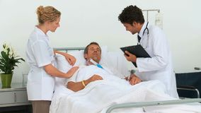 Two doctors visiting a patient. At the hospital stock footage